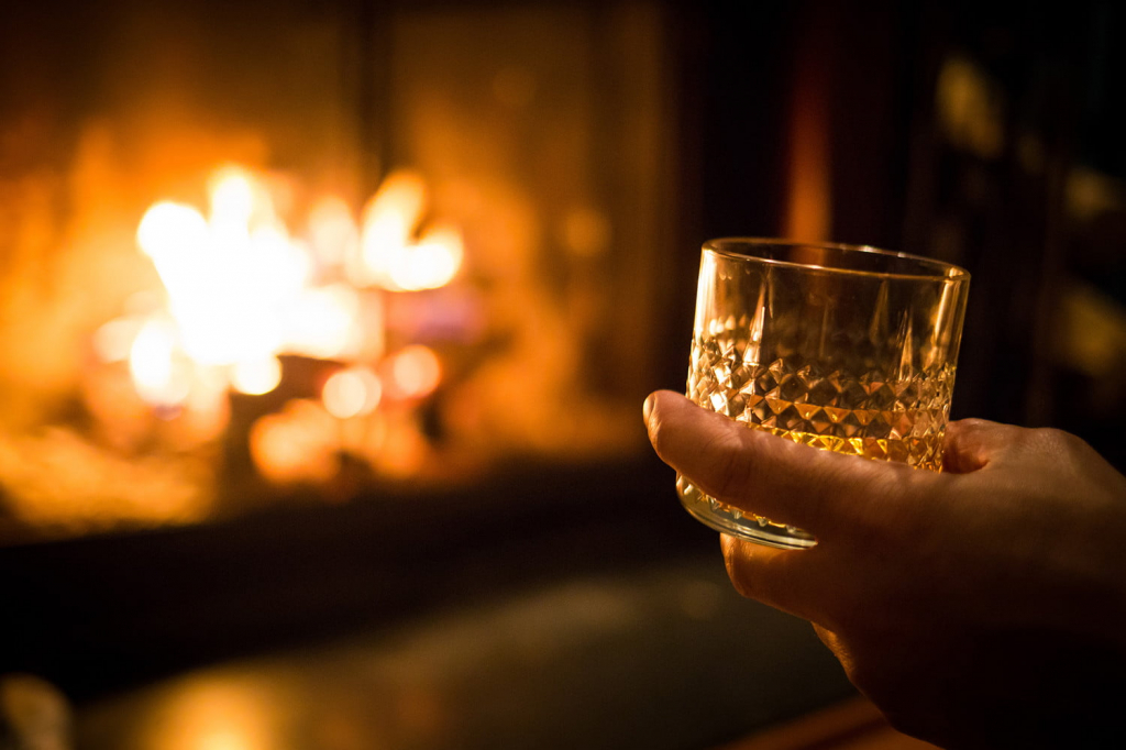 hand-holding-whiskey-glass-at-fireplace.jpg